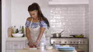 Front view of woman chopping ingredients at kitchen table, shot on R3D video