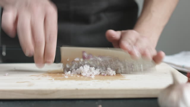 Front view of yong man cook cut thin slices of red onion with knife on cutting Board. video