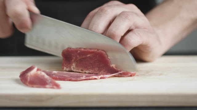 Front view of young man chef cut thin slices of meat with knife on cutting Board. video