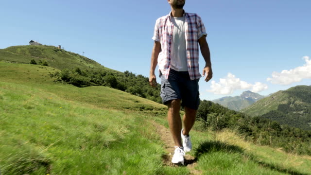 Front view of young man hiking in mountain outdoor nature scenery during sunny summer day - gimbal steadicam HD video footage video