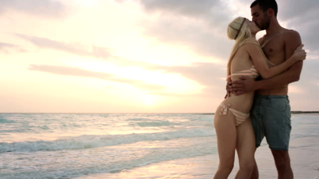 Front view of young man-woman couple in love enjoys and walks along ocean beach sea-side at sunrise or sunset in summer - gimbal steadicam HD video footage video