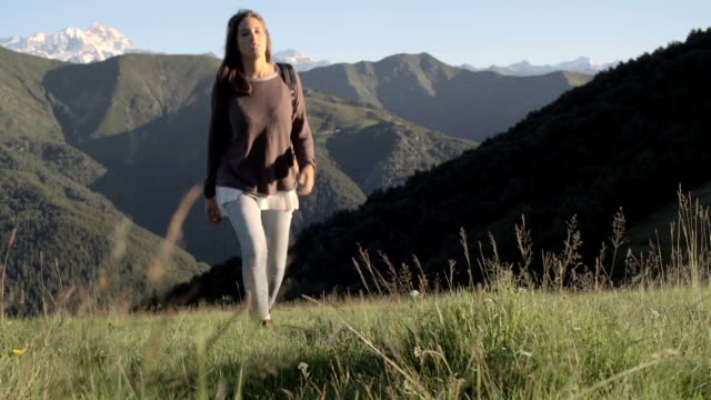 Front view of young woman hiking toward camera in mountain outdoor nature scenery during sunny summer day - HD video footage video