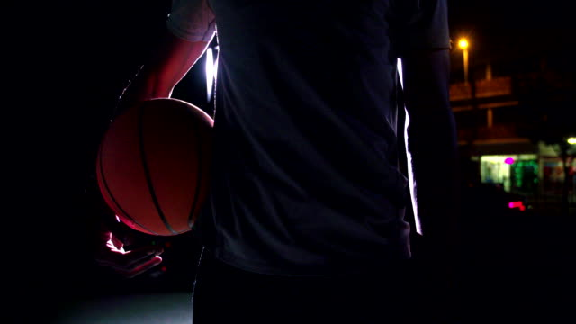 Frontal key shot of basketball player holding ball on hip video