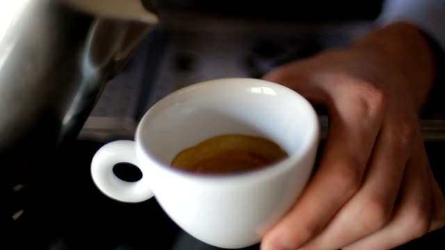 frothed milk is poured into a cup of coffee. cappuccino preparation video