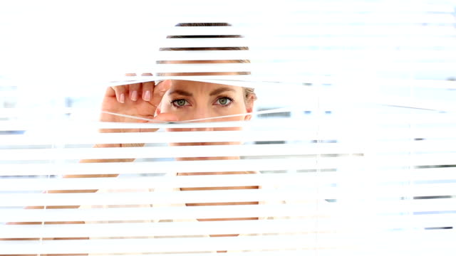Frowning businesswoman peeking through the blinds video