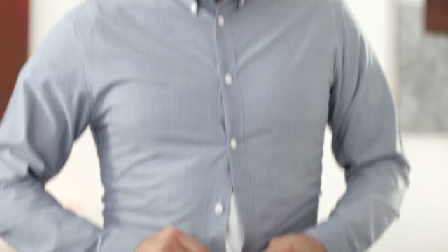 Frustrated angry man trying to button up a tight shirt video