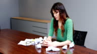 Frustrated female executive sitting with crumpled papers balls video
