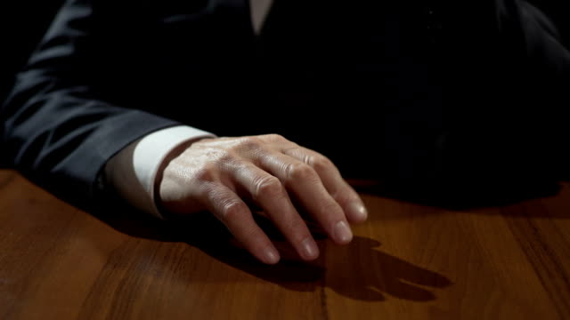 Frustrated mafia boss drumming fingers on table, thinking or making decision video