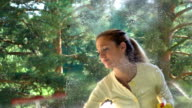 Frustrated, tired woman washes a window with a special detergent spray and a brush. Dolly shot. video