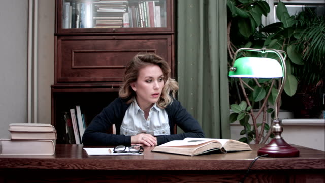 Frustrated woman impatiently looking at papers and books on her desk slamming her fists on the table video