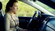 A frustrated woman with a phone sits in the car. Ready to cry, very sad. Concept - depression, women's problems video