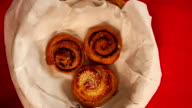 Full  basket of sweet bread rolls with cinnamon and sesame seeds  stop motion overhead shot video