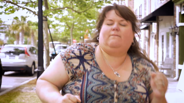 Full figured happy woman dancing on the sidewalk in a small city video