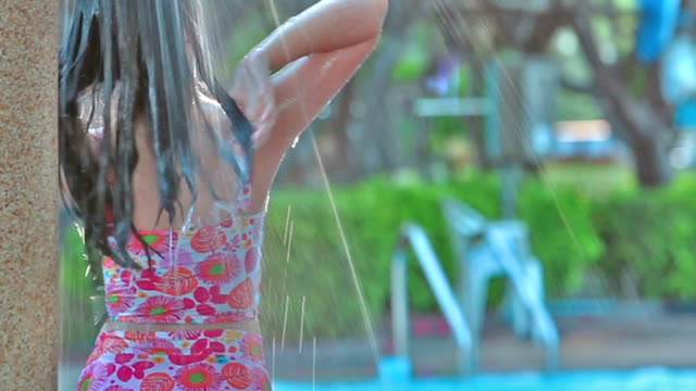 Full HD, Relaxed Arian girl teen in out-door shower on swimming pool. video