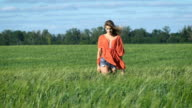 Full lenght portrait of a beautiful blonde young romantic woman in a red shirt walking slowly touching the grass at the green field video