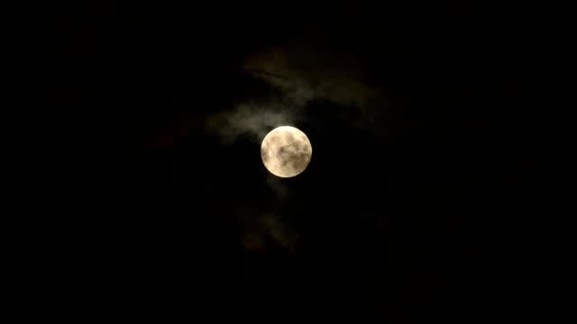 Full moon behind dark clouds video
