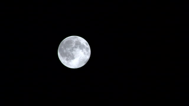 Full moon on a dark night appearing and then disappearing video