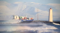 Fully loaded cargo ship sails by snowy mountains, Grotta lighthouse Iceland video