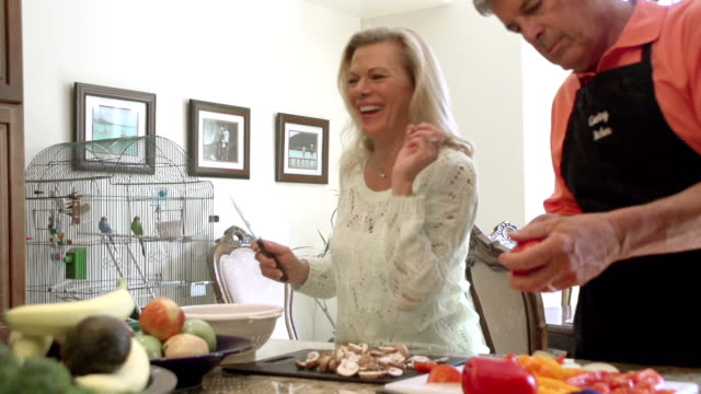 SLOW MOTION - Fun Mature Preparing Food in Kitchen. video