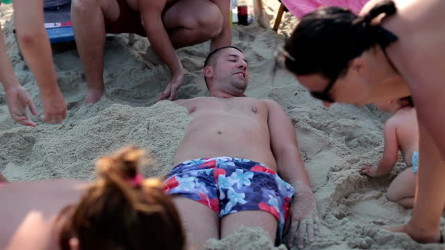 fun on vacation , enjoying on travel - family is burying man on the beach video