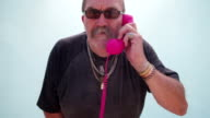 Funny angry senior man holding pink phone hendset video