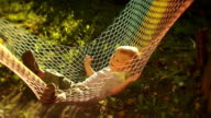 Funny boy 1.5 years swinging in the hammock in the garden at sunset video