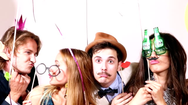 Funny couples playing with props in party photo booth video