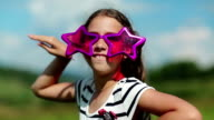 Funny girl in big glasses in shape of stars looks at the camera and makes faces video