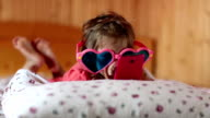 Funny girl in big glasses in the shape of hearts with smartphone lies on the bed video