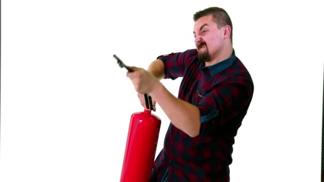 Funny guy posing as a firefighter and pointing a fire extinguisher at imaginery fire video