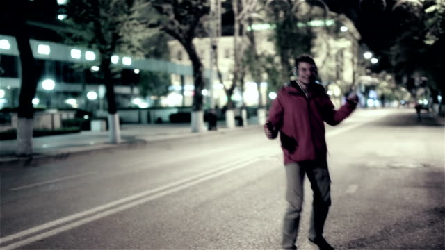 Funny guy walk down the night street city, free dancing to music in headphones video