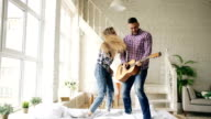 Funny happy and loving couple dance on bed singing with tv controller and playing guitar. Man and woman have fun during their holiday at home video