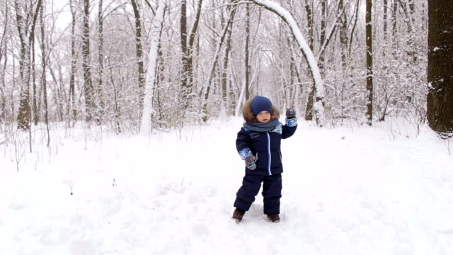 Funny kid playing in winter Park. Winter landscape video