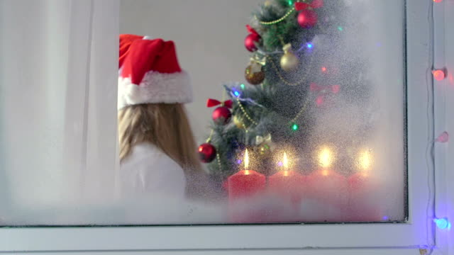 Funny kids celebrate Christmas around a decorated tree view through the window video