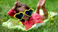Funny little girl in sunglasses in shape of hearts lies on grass and grimaces video