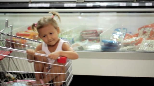 Funny little girl ride in a grocery cart at a supermarket video