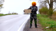 Funny man hitchhiking under rain to Hollywood, Pumpkinhead stay at roadside video