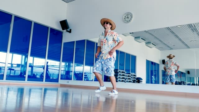 Funny man in sunglasses and hat dancing in gym video