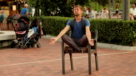 Funny man meditating in lotus position on chair at park, video