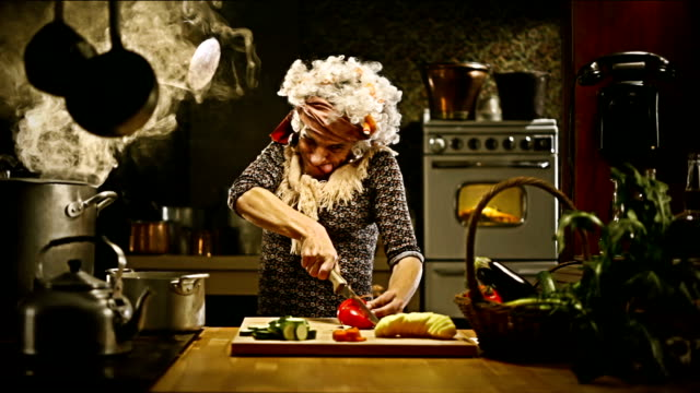 Funny old lady cuts vegetables in the kitchen video