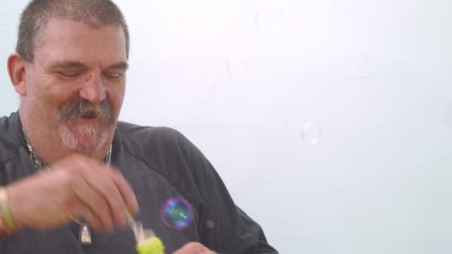 Funny senior man blowing soap bubbles video