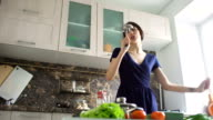 Funny woman housewife cook dance and sing with big ladle while cooking in modern kitchen at home video