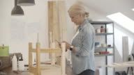 4K: Furniture Designer Using Smart Phone In Her Workshop. video
