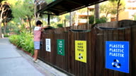 Garbage separation. Child throwing apple, plastic bottle into the trash video