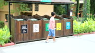 Garbage separation. Child throwing plastic bottle into the trash video