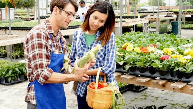 Garden store employee helps Vietnamese woman choose vegetables video