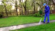 Gardener man wash footpath with high pressure water jet. video