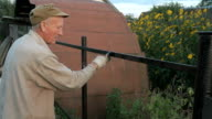 Gardener painting the iron fence using black paint video