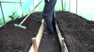 Gardener prepare soil bed with raker tool in hothouse. video