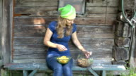 Gardener woman with knife clean chanterelle mushrooms on bench video